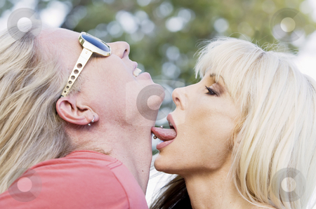 Rock and Roll Couple stock photo, Woman with big eyes licking a man on the neck by Scott Griessel