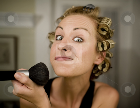 Woman Applying Makeup stock photo, Woman in Curlers Applying Makeup with a Brush by Scott Griessel