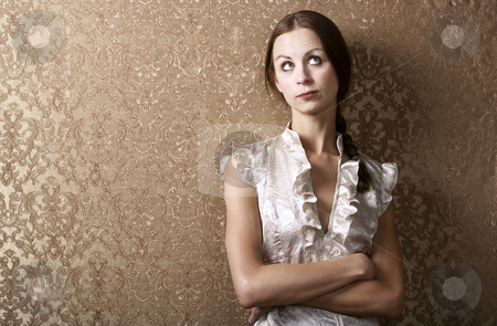 Young Woman Leaning Against a Wall stock photo, Pretty young woman waiting leaning up against a wall with gold wallpaper by Scott Griessel