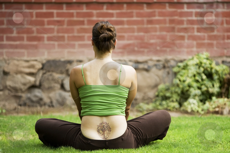 Woman with tattoo stock photo, Back of woman with a tattoo sitting on grass by Scott Griessel