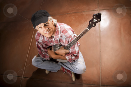 Banjo Player Sitting on Cement stock photo, Banjo Player Sitting Indoors on Cement Floor by Scott Griessel
