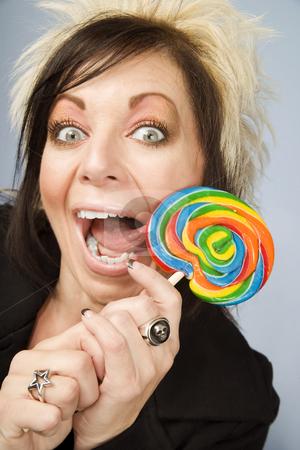 Creative Businesswoman with a Lollipop stock photo, Portrait of a creative businesswoman with wild hair licking a lollipop by Scott Griessel