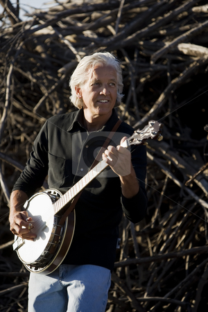 Banjo Player Outdoors stock photo, Banjo Player in Front of a Big Pile of Wood by Scott Griessel