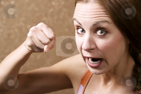 Angry Woman Throwing a Punch stock photo, Angry Young Woman in Front of Gold wallpaper Throwing a Punch by Scott Griessel