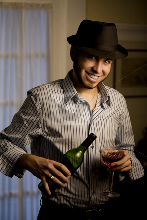 Young Man in a Fedora with Red Wine stock photo, Handsome Young Man Indoors Wearing a Fedora Hat and Red Wine by Scott Griessel