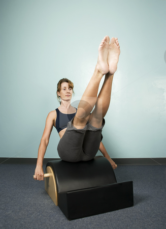 Woman Exercising stock photo, Athletic Woman Exercising and Balancing on Gym Equipment by Scott Griessel