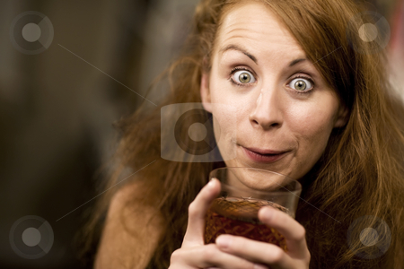 Woman sipping a cocktail stock photo, Woman with big eyes and hair sipping cocktail by Scott Griessel
