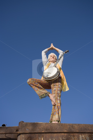 Banjo Player in a Yoga Pose stock photo, Banjo player standing in a Yoga pose against the blue sky by Scott Griessel