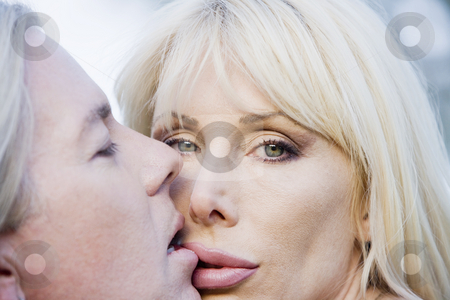 Rock and Roll Couple stock photo, Close up of a pretty woman kissing a man by Scott Griessel
