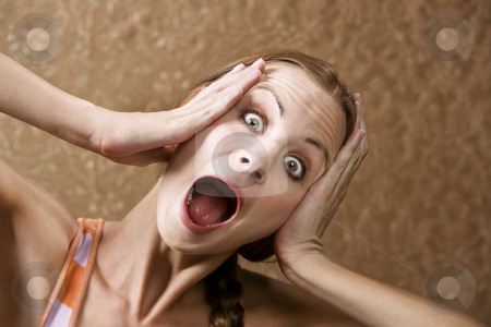 Horrified Woman stock photo, Horrified Young Woman in front of Gold wallpaper by Scott Griessel