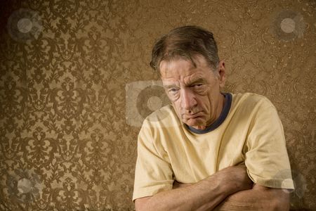 Senior Man with his Arms Crossed stock photo, Senior Man Against a Gold Background with a Stern Expression and Arms Crossed by Scott Griessel