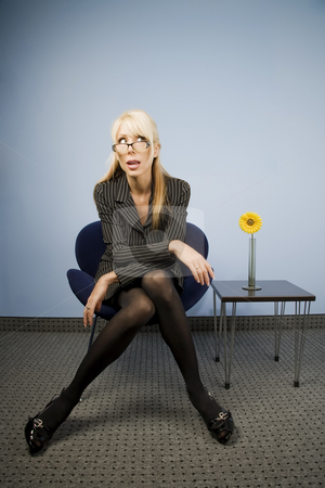 Woman Looking Over Her Glasses stock photo, Businesswoman sitting and looking over the top of her glasses by Scott Griessel