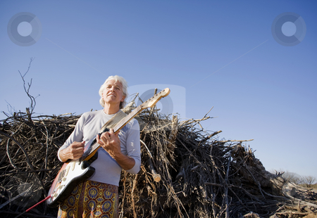 Electric Guitar Player Outdoors stock photo, Electric Gutiar Player in Front of a Big Pile of Wood by Scott Griessel
