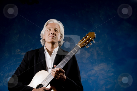 Classical Guitarist stock photo, Classical Guitarist with his Instrument in front of a Blue Wall by Scott Griessel