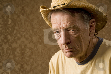 Man in a Cowboy Hat stock photo, Senior man in a straw hat in front of gold wallpaper by Scott Griessel