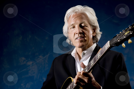 Guitarist stock photo, Guitarist with his Instrument in front of a Blue Wall by Scott Griessel