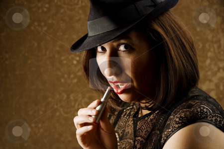Hispanic Woman Applying Makeup stock photo, Pretty Hispanic Woman in a Fedora Applying Lipstick by Scott Griessel