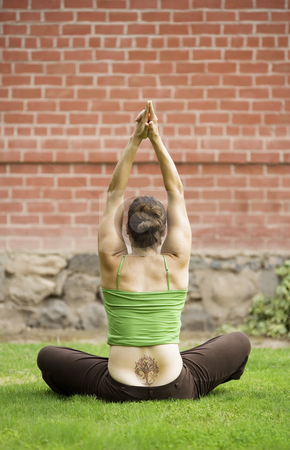 Woman lotus pose stock photo, Back of woman with a tattoo sitting on grass doing yoga by Scott Griessel