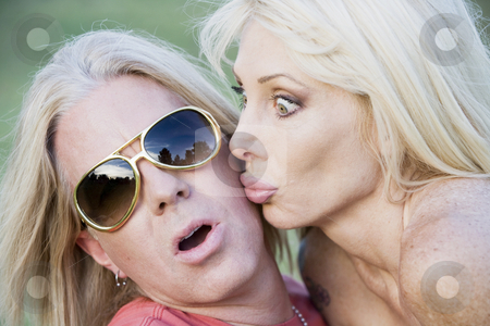 Rock and Roll Couple stock photo, Woman with big eyes kissing a surprised and pleased man by Scott Griessel