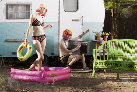 Women outside a trailer stock photo, Women doing summer activities outside a travel trailer by Scott Griessel