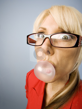 Woman in red blowing a bubble stock photo, Woman in red with glasses blowing a bubble by Scott Griessel
