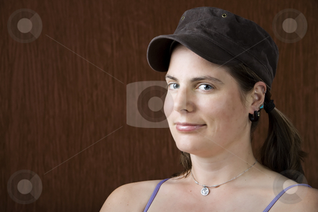 Woman with blue eyes stock photo, Closeup of woman with blue eyes wearing a cap by Scott Griessel