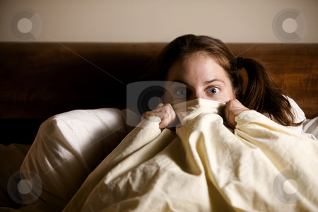 Frightened Woman in Bed stock photo, Frightened Woman in Bed with the Sheets Pulled Up to her Face by Scott Griessel