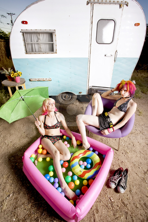 Women in front of a trailer stock photo, Woman relaxing with in an inflatable play pool by Scott Griessel