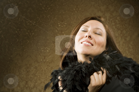 Pretty Hispanic Woman Wearing Feathers stock photo, Pretty Hispanic Woman Wearing a Feather Boa in front of Gold Wallpaper by Scott Griessel