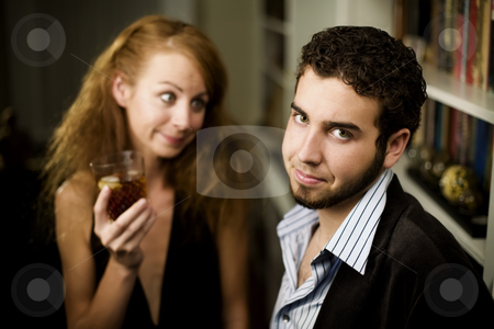 Woman looks lovingly at young man stock photo, Young woman with big hair looks lovingly at young man by Scott Griessel