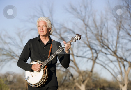 Banjo Player Outdoors stock photo, Banjo Player in Front of a Bare Trees by Scott Griessel