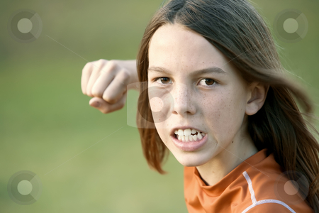 Boy with Long Hair Throws a Punch stock photo, Boy with Long Hair Throws a Punch at the Camera by Scott Griessel