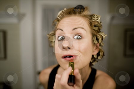 Woman Applying Lipstick stock photo, Woman in Curlers Applying Bright Red Lipstick by Scott Griessel