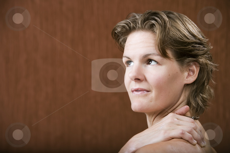 Woman with her hand on her shoulder stock photo, Woman with her hand on her shoulder looking left by Scott Griessel