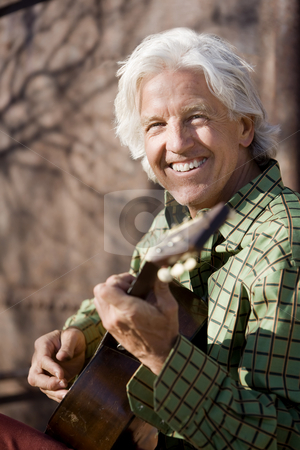 Handsome guitar player stock photo, Handsome man playing an old acoustic guitar by Scott Griessel