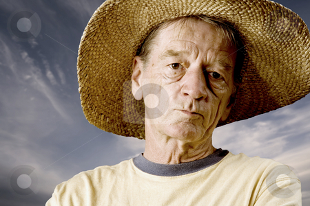 Man in a Big Straw Hat stock photo, Senior in a straw hat in front of cloudy sky by Scott Griessel