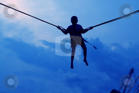 Silhouette at the park stock photo, Evening silhouette of a youngster having fun on the bungee jumping at the fair by Jack Schiffer