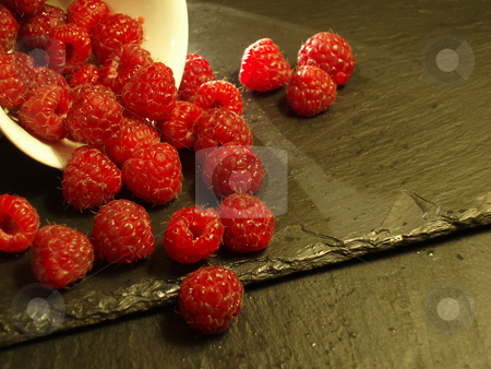 Raspberries stock photo, Ripe red raspberries spilling from a cup by Stephen Gibson