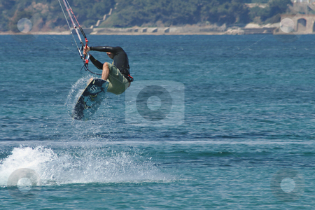 Flying in Kite stock photo, Kiteboarder taking off for a jump in front of windsurfer by Serge VILLA