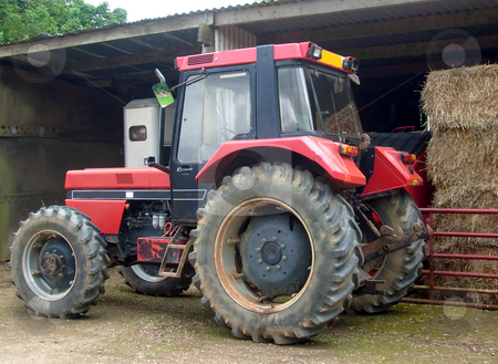 Red farm tractor stock photo, Close up of farm tractor by barn. by Martin Crowdy