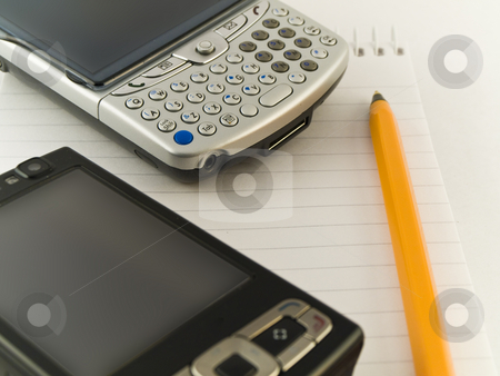 Mobile Phones and Pen on Notepad White Background stock photo, Mobile Phones and Pen on Notepad White Background by Robert Davies