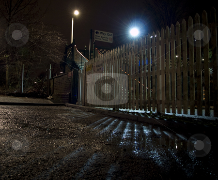 Fence Near Train Station at Night stock photo, Fence Near Train Station at Night With Light Behind by Robert Davies