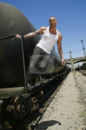 Man grabbing train stock photo, Male fashion model  posing on train by Csaba Fikker