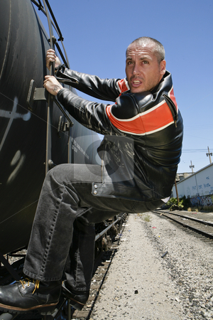 Man riding the side of a train stock photo, Man holding onto the side of a train and riding it. by Csaba Fikker