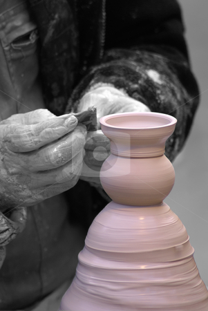 Throwing pot on pottery wheel stock photo, Desaturated pict of a Potter finishing a pink Jar by Serge VILLA