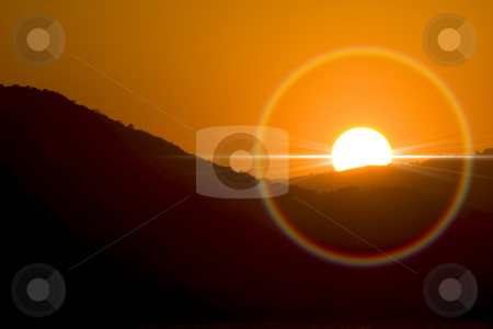 Sunset stock photo, Sunset and ray of sun rounded bty an halo. by Serge VILLA