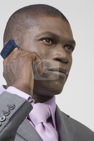 Black Businessman listening to phone stock photo, Black Businessman listening to his phone by Csaba Fikker