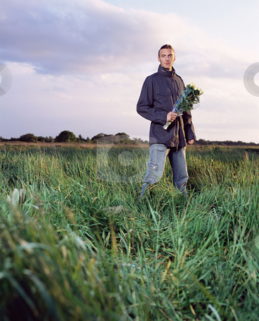 MPIXIS900776 stock photo, Man in a field holding a bunch of roses by Mpixis World
