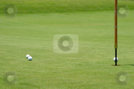 Golf balls near flagstick stock photo, Three golf balls near the flagstick on the green. by Henrik Lehnerer