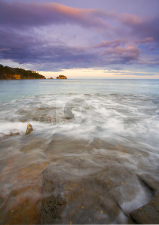 Sunset Grooves stock photo, The setting sun illuminates the cliffs of the Tasman Peninsula as the tides flow over the Tesselated Pavement in the foreground. by Mike Dawson